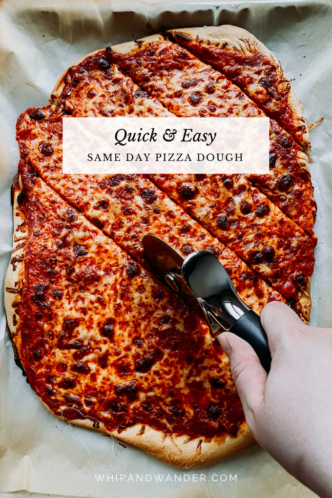 a hand using a pizza wheel to cut diagonal slizes into a baked cheese pizza