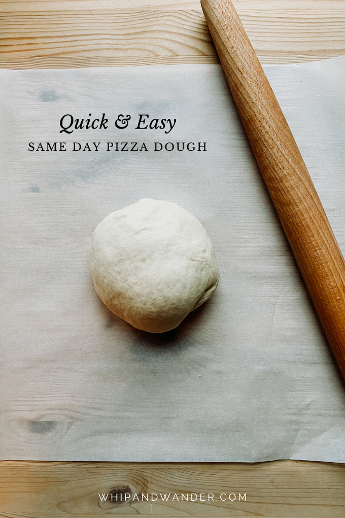 a ball of pizza dough resting on a piece of white parchment paper with a French rolling pin resting on top next to the dough