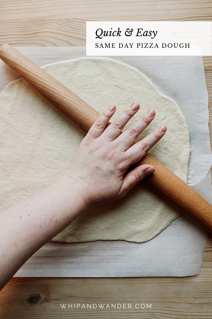 a hand rolling pizza dough out on a piece pf parchment paper with a French rolling pin