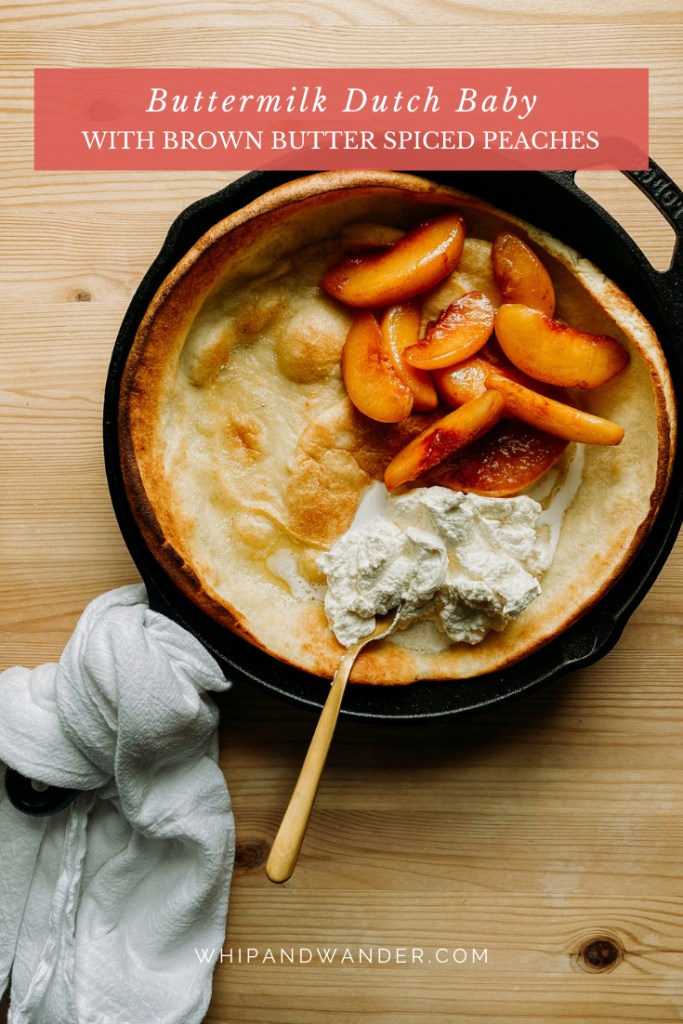 fresh whipped cream being spooned onto a Buttermilk Dutch Baby with cooked peaches in brown butter