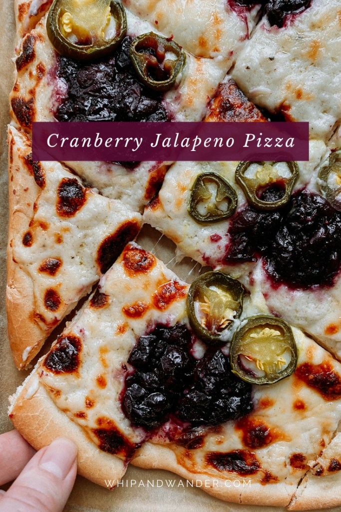 a hand pulling apart a piece of cranberry jalapeno pizza with garlic cheese sauce and mozzarella and parmsan cheese