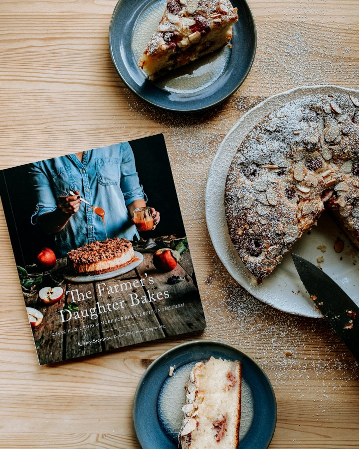 The Farmer's Daughter Bakes cookbook resting on a wooden surface next to a plate of cake and two smaller plates with slices of cake