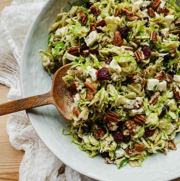 a wooden spoon dishing into a white bowl of Shaved Brussels Sprouts Salad with Blue Cheese, Cranberries, and Pecans