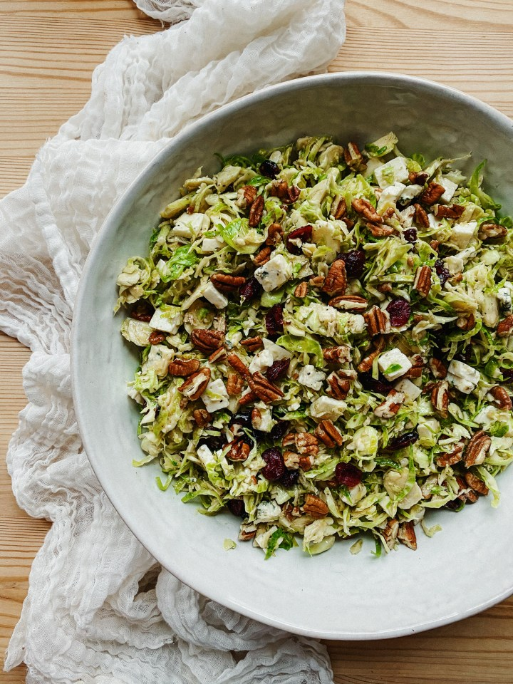 a white dish filled with Shaved Brussels Sprouts Salad with Blue Cheese, Cranberries, and Pecans on a white twoel