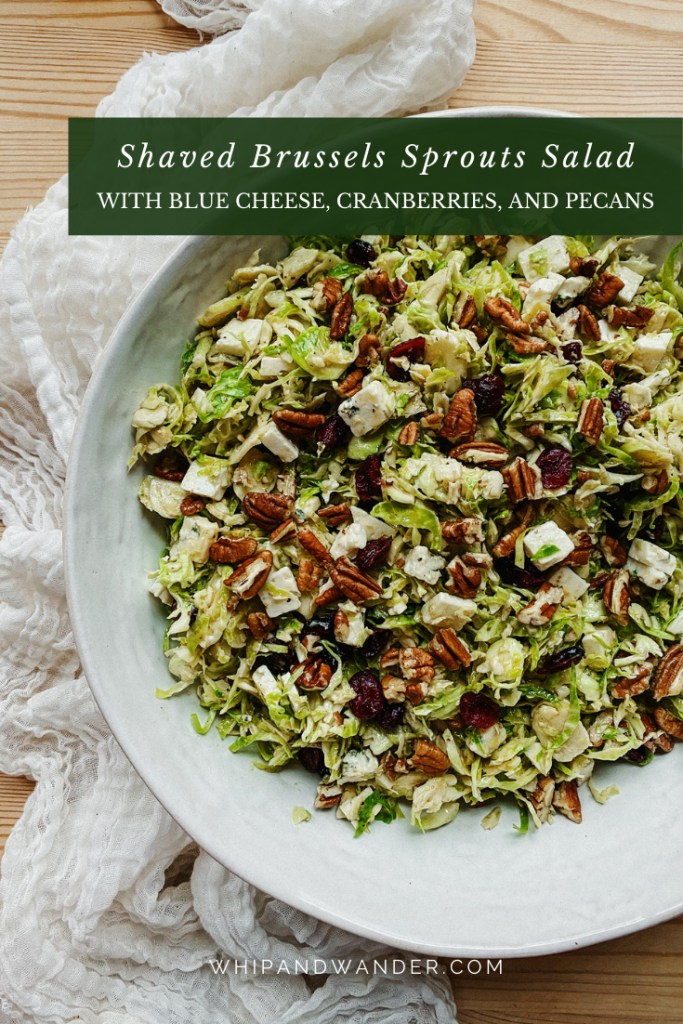 a white bowl filles with a shaved brussels sprouts salad tossed with dressing, cranberries, blue cheese, and nuts