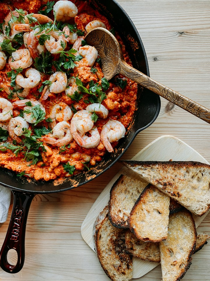 a wooden spoon resting in a skillet of Shrimp in Romesco Sauce with White Beans with a board of toast points resting nearby