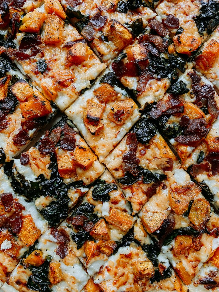 closeup of pumpkin, kale, gouda, and bacon on a pizza that has been cut into squares