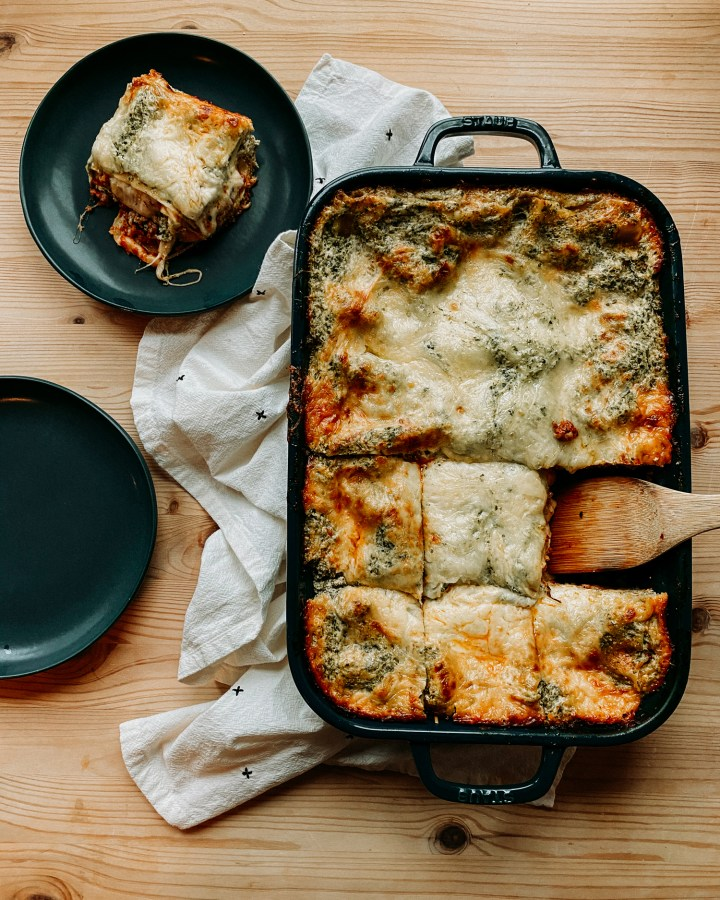 Christmas Eve Lasagna in a large teal pan on a white towel on a wooden surface with two teal plates resting nearby on the surface