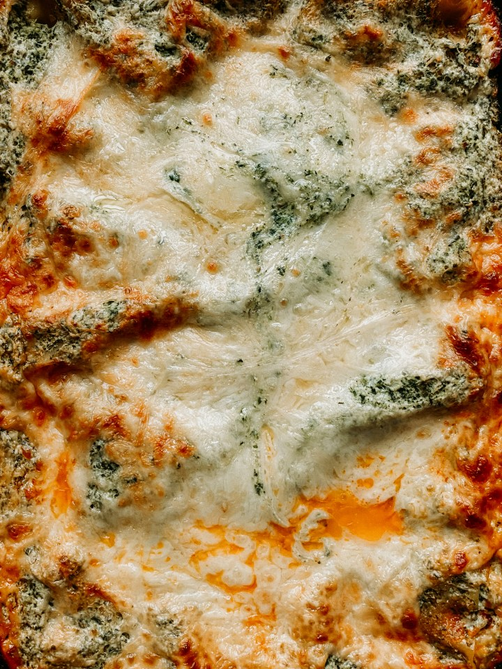a closeup of melted cheese and spinach ricotta on a baked lasagna