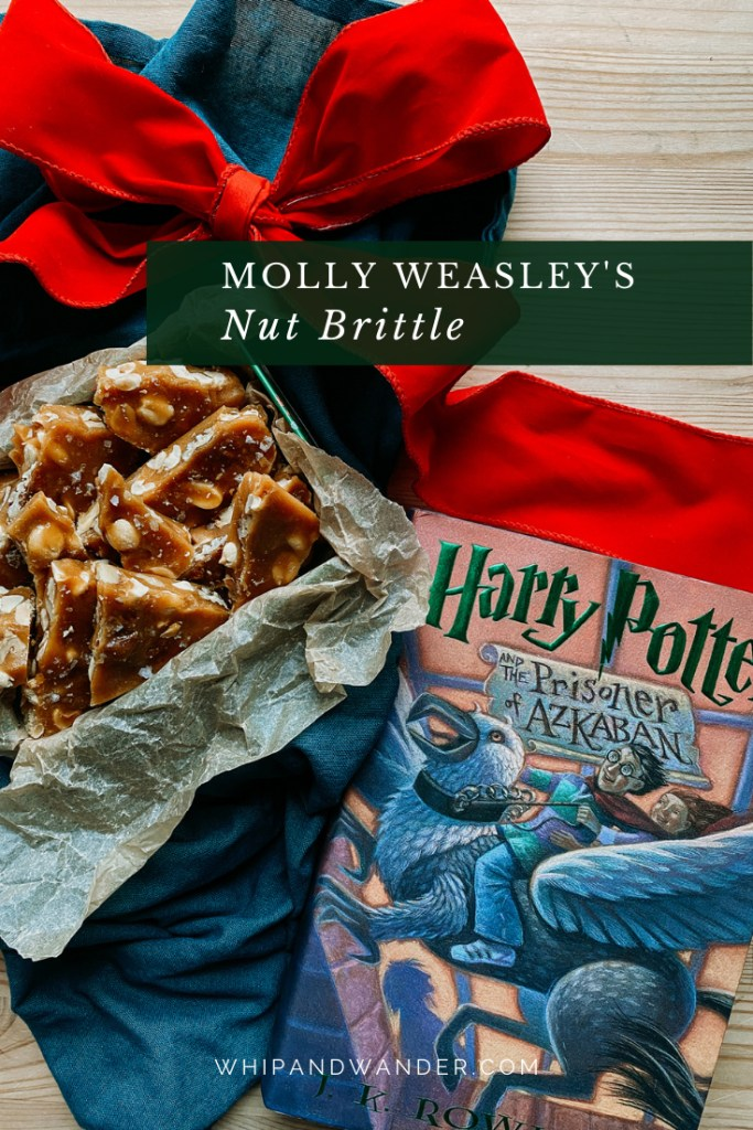 a large red ribbon, a harry potter book, and a tin of Molly Weasley's Nut Brittle resting on a wooden surface with a dark blue towel