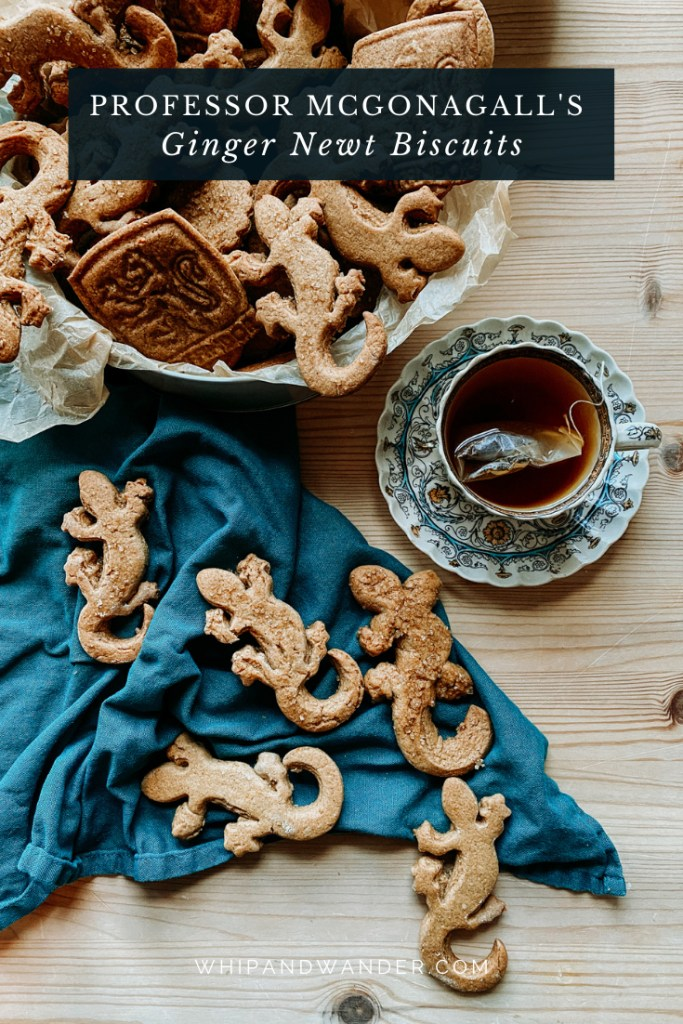 a cup and saucer of black tea resting next to a dark teal towel covered in Professor McGonagall's Ginger Newt Biscuits with a tin of additional cookies resting nearby