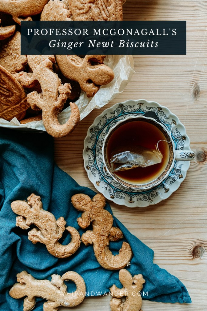 a wooden surface with a cup of black tea on a saucer resting next to a tin filled with Professor McGonagall's Ginger Newt Biscuits and a teal towel with additional biscuits