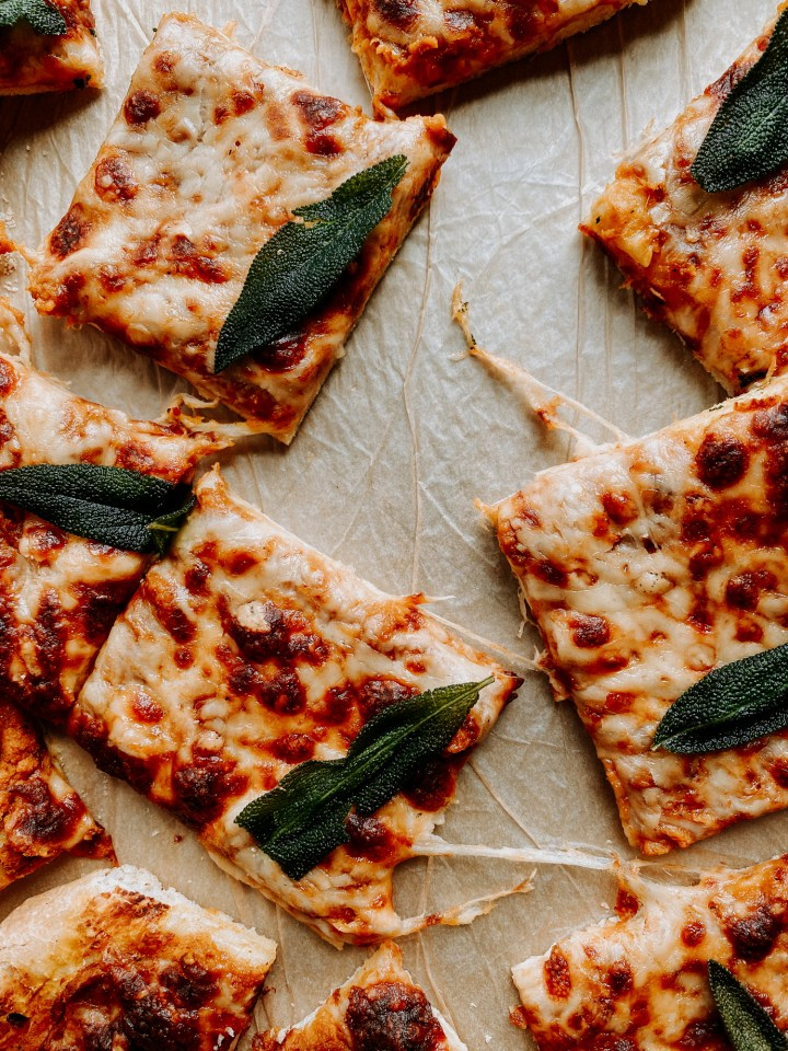 square slices of Pumpkin Pizza with Gruyere and Crispy Sage with lots of cheese tails from being pulled apart