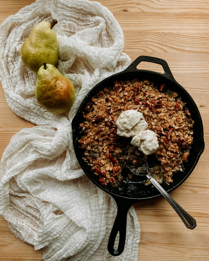 a spoon resting in a cast iron pan containing Spiced Pear Crisp and scoops of vanilla bean ice cream resting on a white towel with two fresh pears