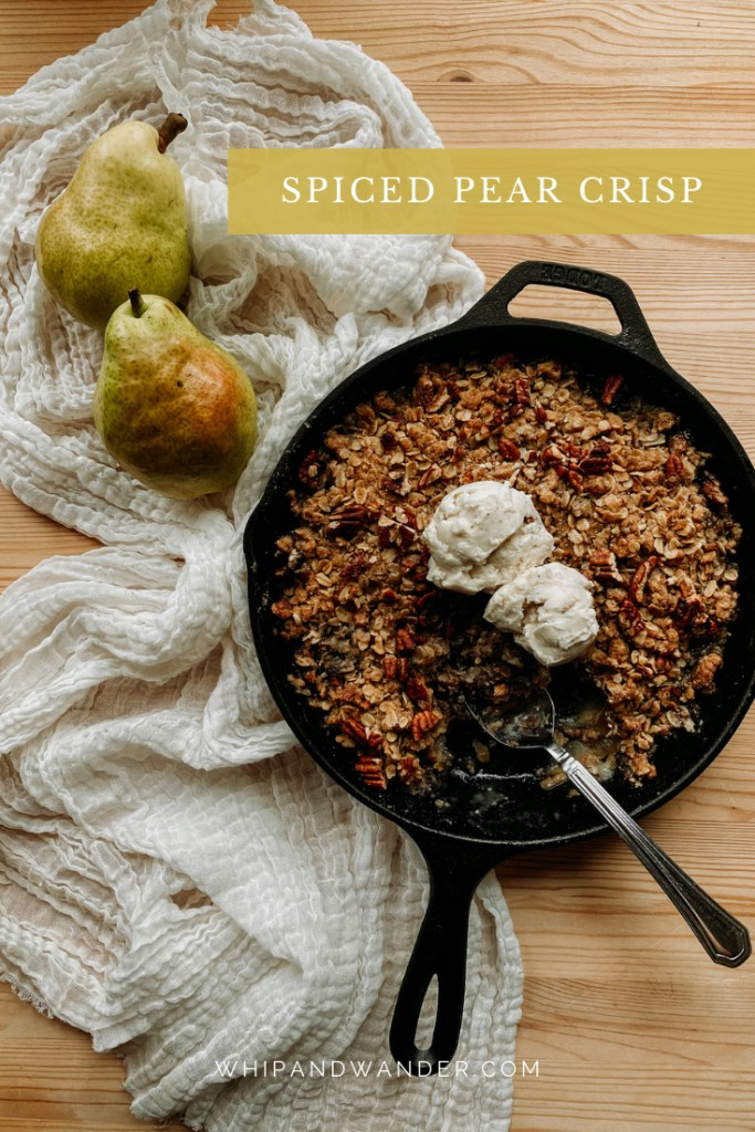 a cast iron pan of Spiced Pear Crisp resting next to a iece of cream colored cloth with two fresh barlett pears resting on top