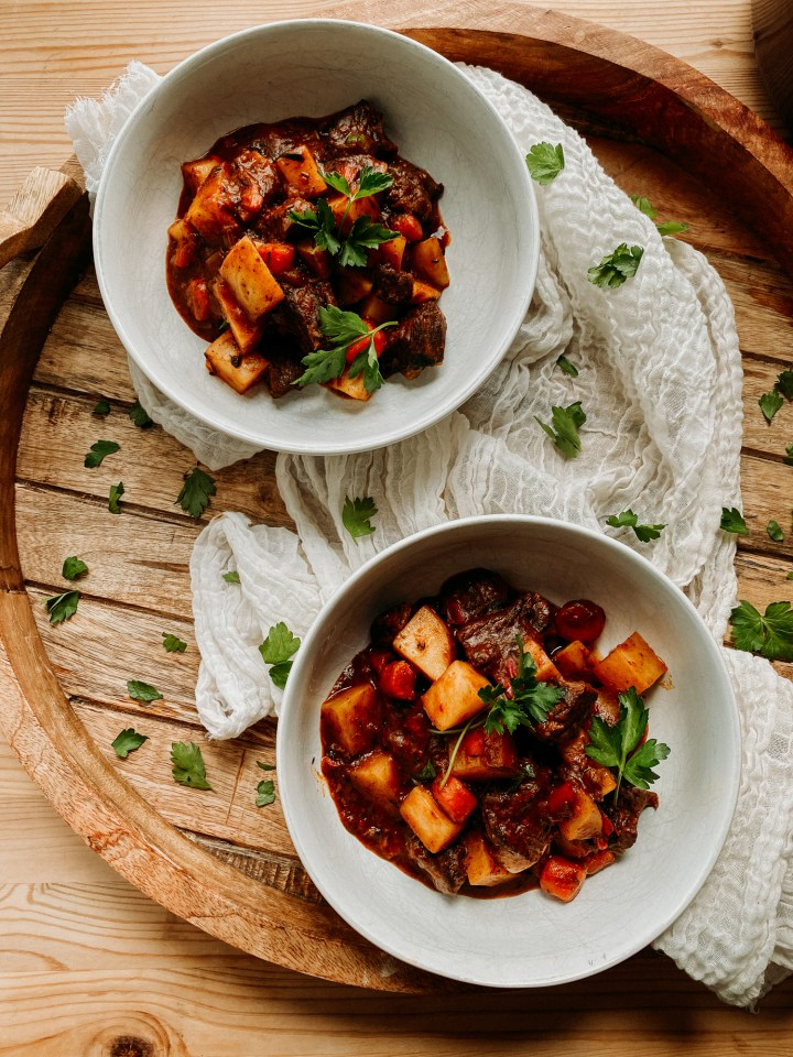 two white bowls willed with goulash on a wooden surface