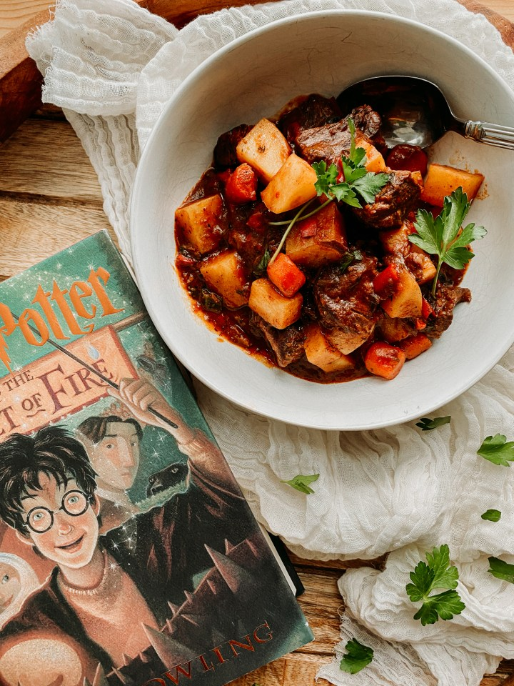 the book harry potter and the goblet of fire on a wooden tray resting next to a white bowl filled with Yule Ball Beef Goulash on a piece of neutral colored cloth