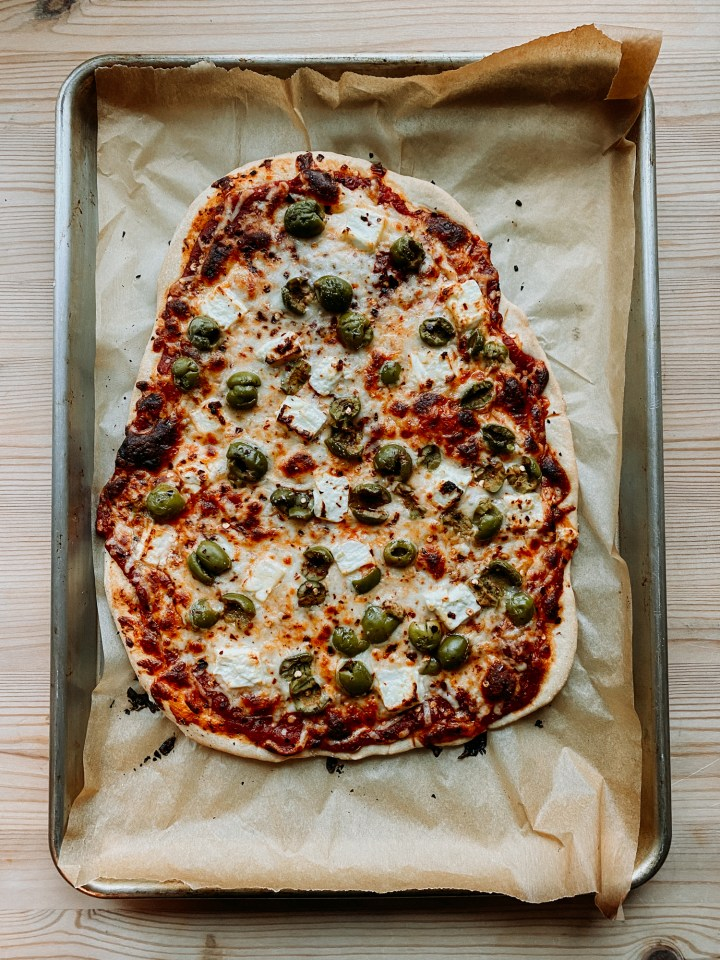 a Green Olive and Feta Pizza fresh out of the oven still resting on it's parchment lines baking sheet on a wooden surface