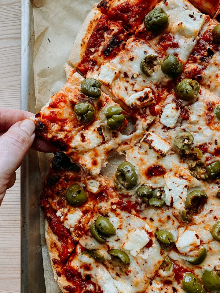 a hand pulling a square slice of pizza covered in olives and feta cheese off of the baking sheet it rests on