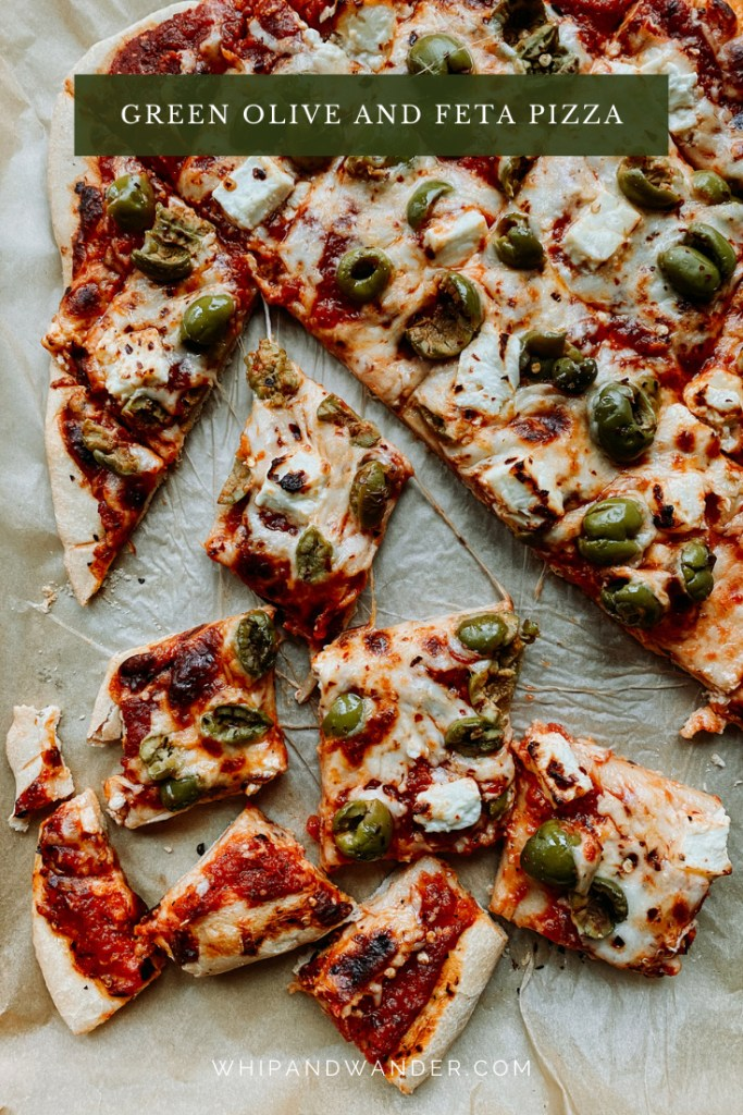 lots of squares od pizza with red peppers feta and greenolive pizza on a baking tray