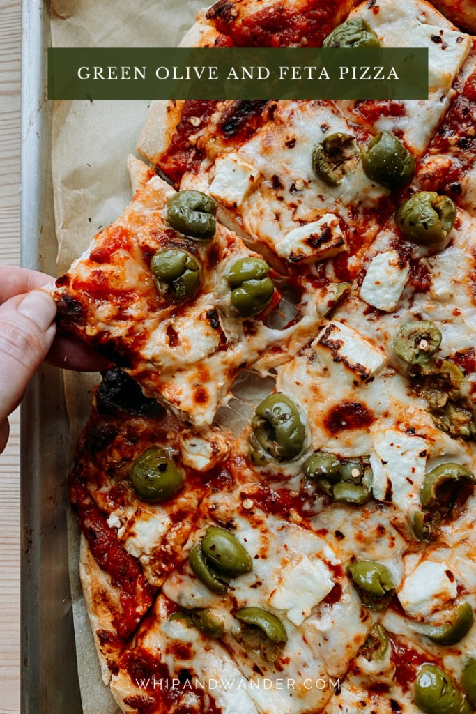 a hand pulling a square slice of pizza topped with red pepper feta and olives away from the larger whole of the piza