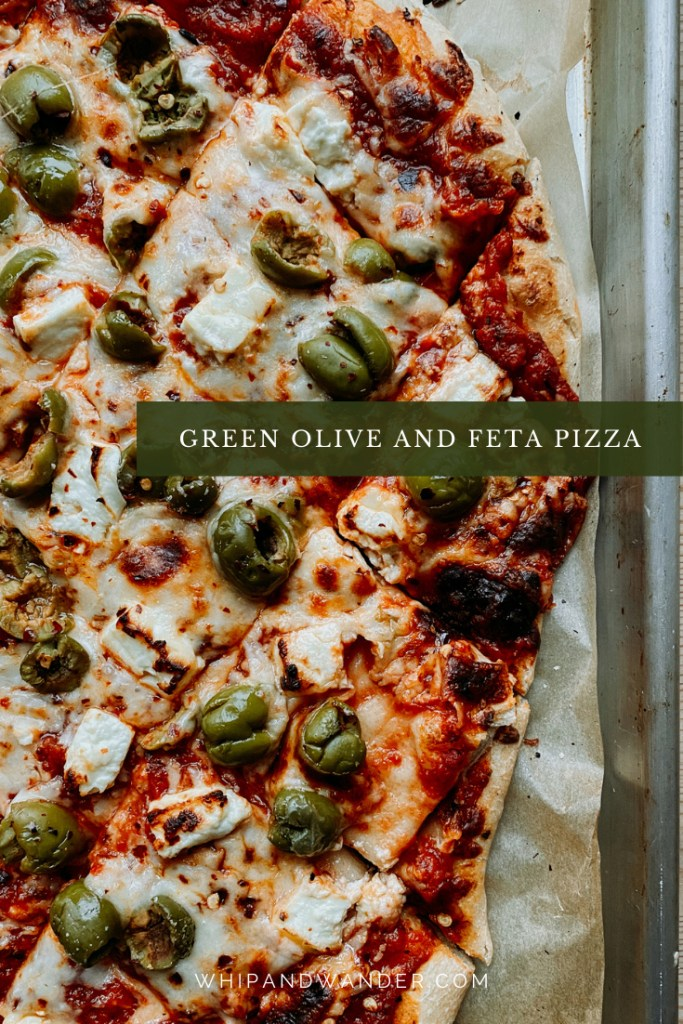 castelvetrano green olives, feta cheese, and red pepper flakes on a pizza cut into squares that is resting on a baking sheet