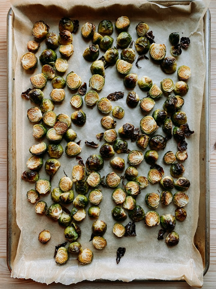 brussels sprouts that have been roasted resting on a parchment lined baking tray on a wooden surface