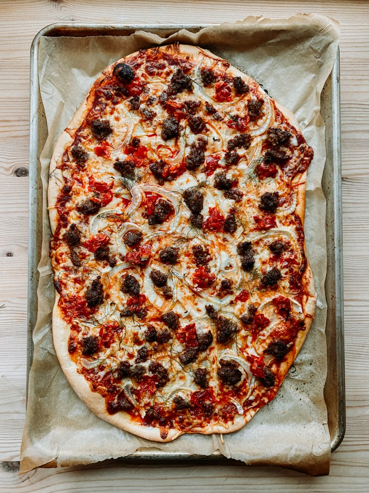 a pizza resting on its parchment lined baking sheet topped with red chili peppers, sausage, and fennel