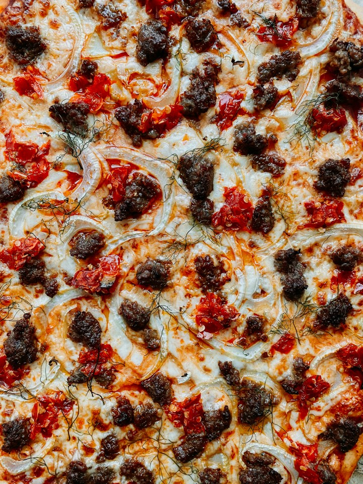 closeup of italian sausage, calabrian chili peppers, fennel, and cheese on a pizza