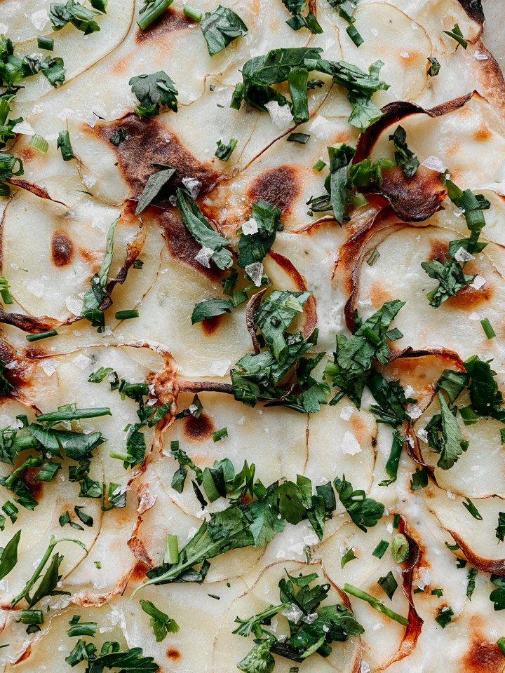 closeup of salt, chives, tarragon, and parsley on a Truffled Potato Pizza with Ricotta and Taleggio