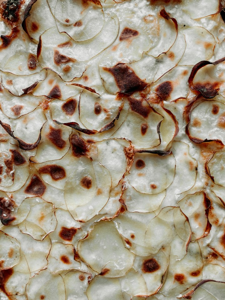 closeup of charred slices of potato on a pizza