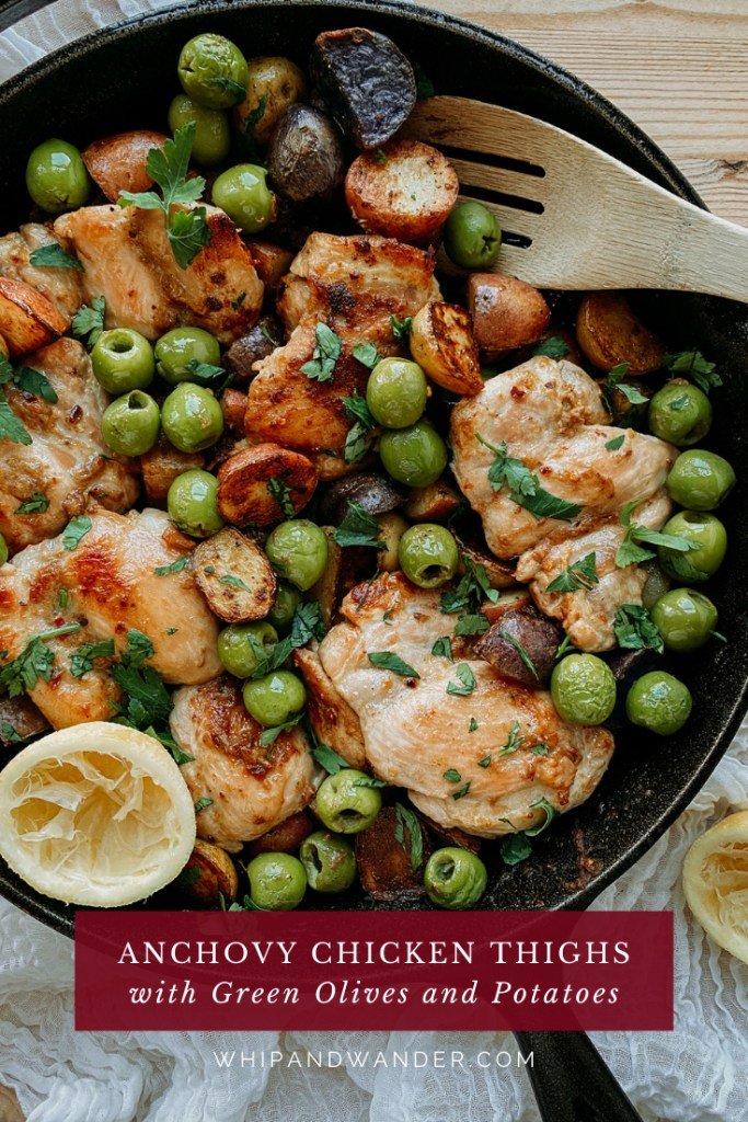 green olives on top of potatoes and chicken in a cast iron pan with a wooden spoon resting in the pan