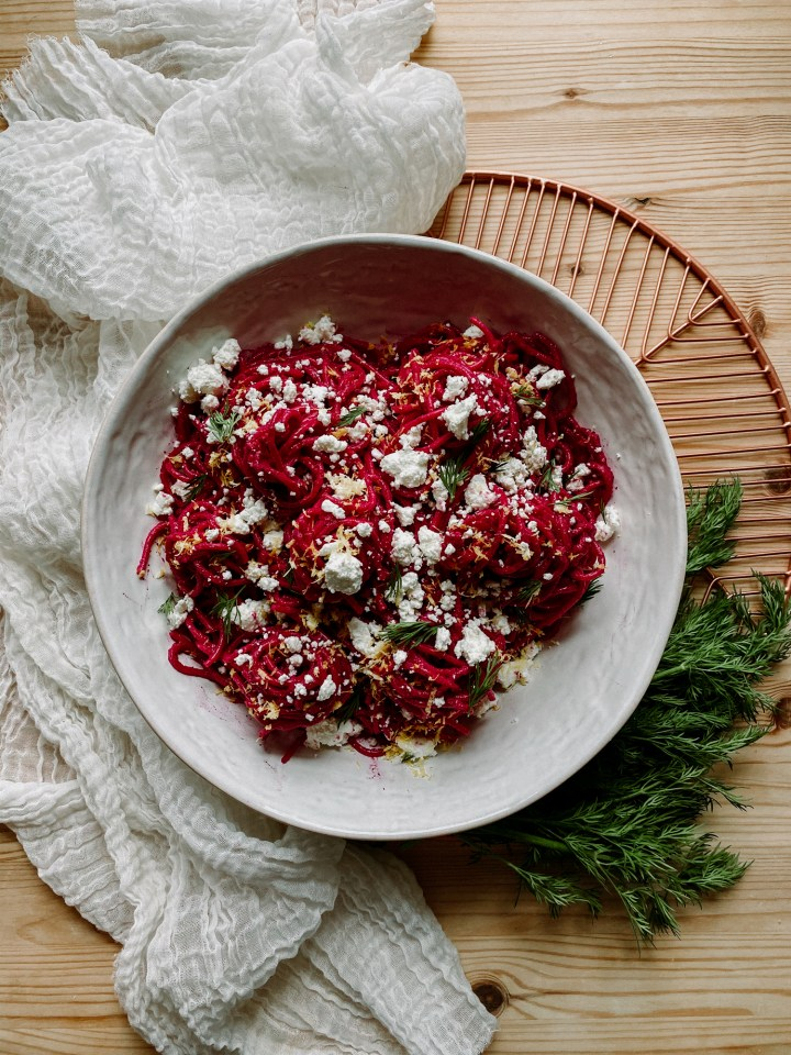 a large white bowl with bright pink pasta, goat cheese, and dill inside, resting on top of a white towel on a copper tray with a large swatch of fresh dill weed on a wooden surface