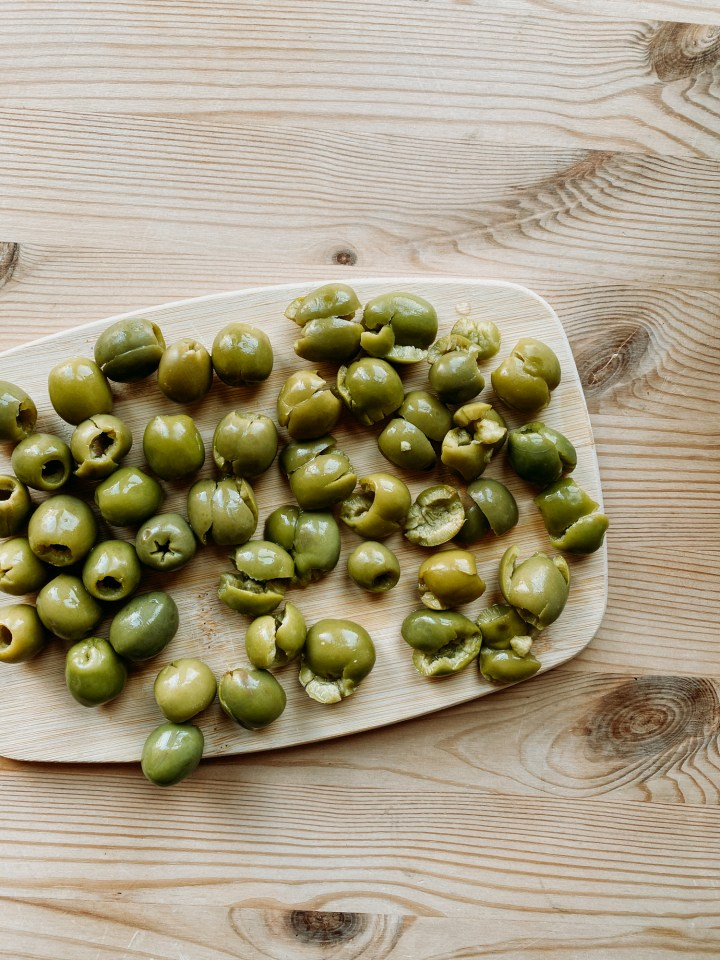 a wooden board covered with green castelvetrano olives on a wooden surface