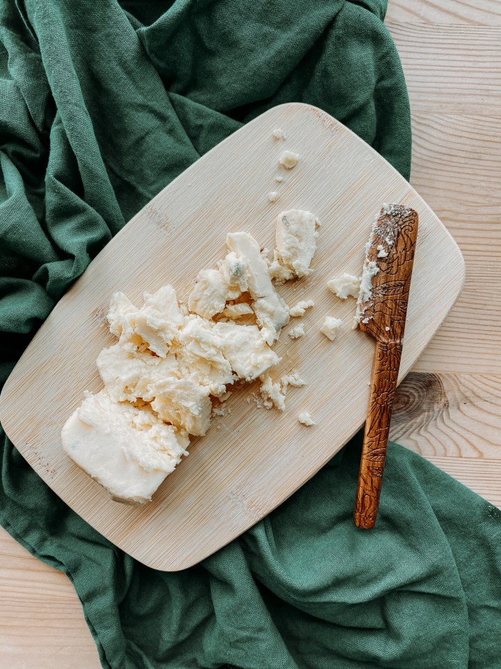 a wooden board with a wedge of gorgonzola blue cheese that has been crumbles with a wooden cheese knife that is resting on the board which is resting on a dark green towel on a wooden surface