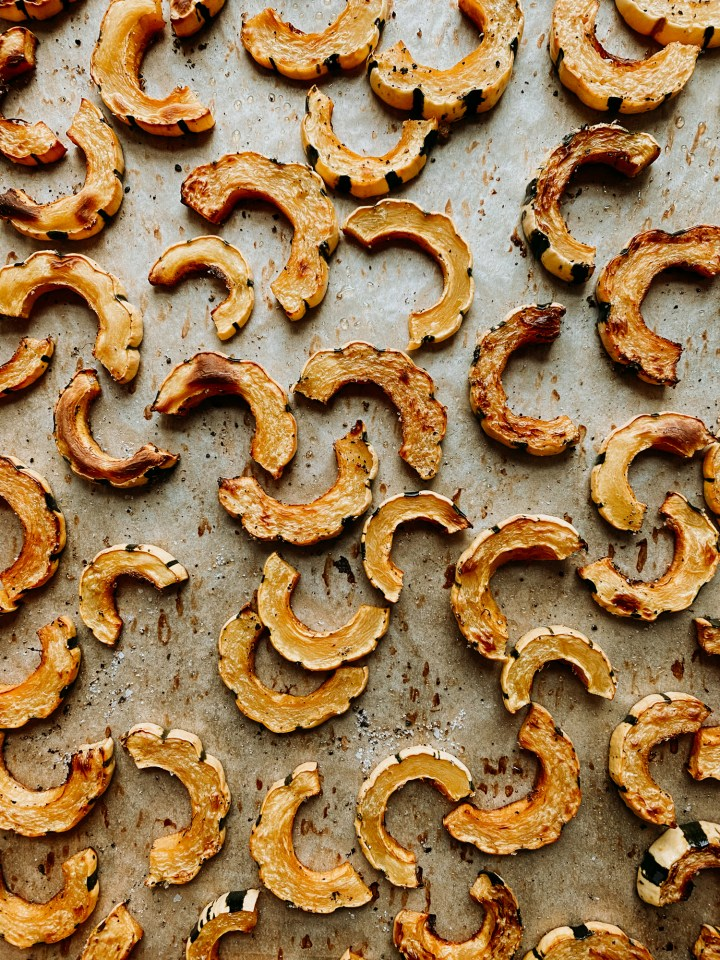baked delicata squash half moons that have been roasted on a baking sheet