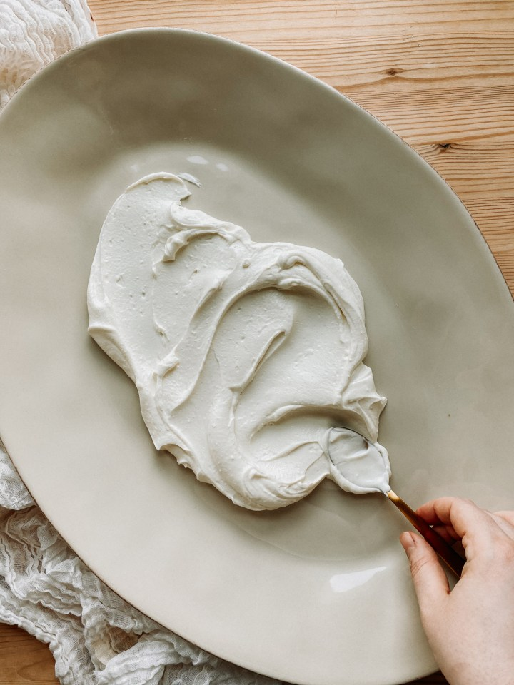 a hand spooning whipped feta across a large serving platter