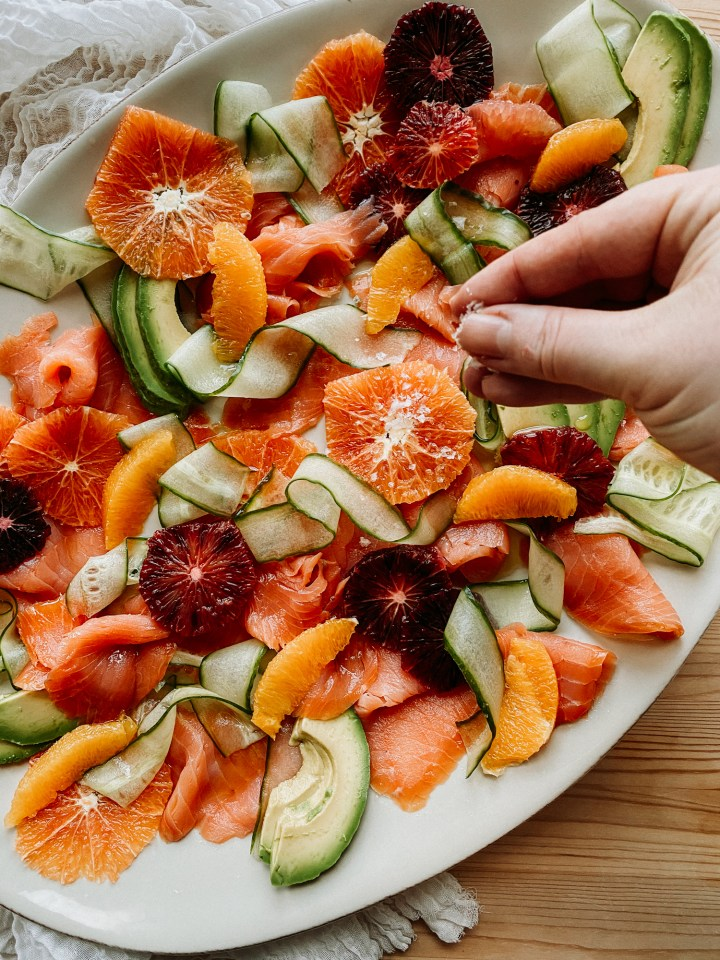 a hand sprinkling salt flakes over the top of a citrus and salmon salad