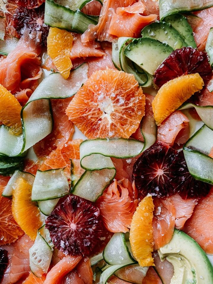 closeup of avocado, citrus, salmon, cucumber, salt, and olive oil