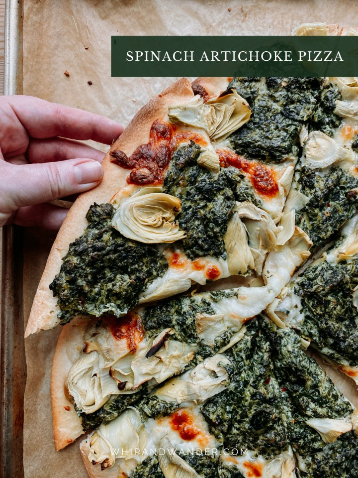 a hand holding a slice of spinach artichoke pizza