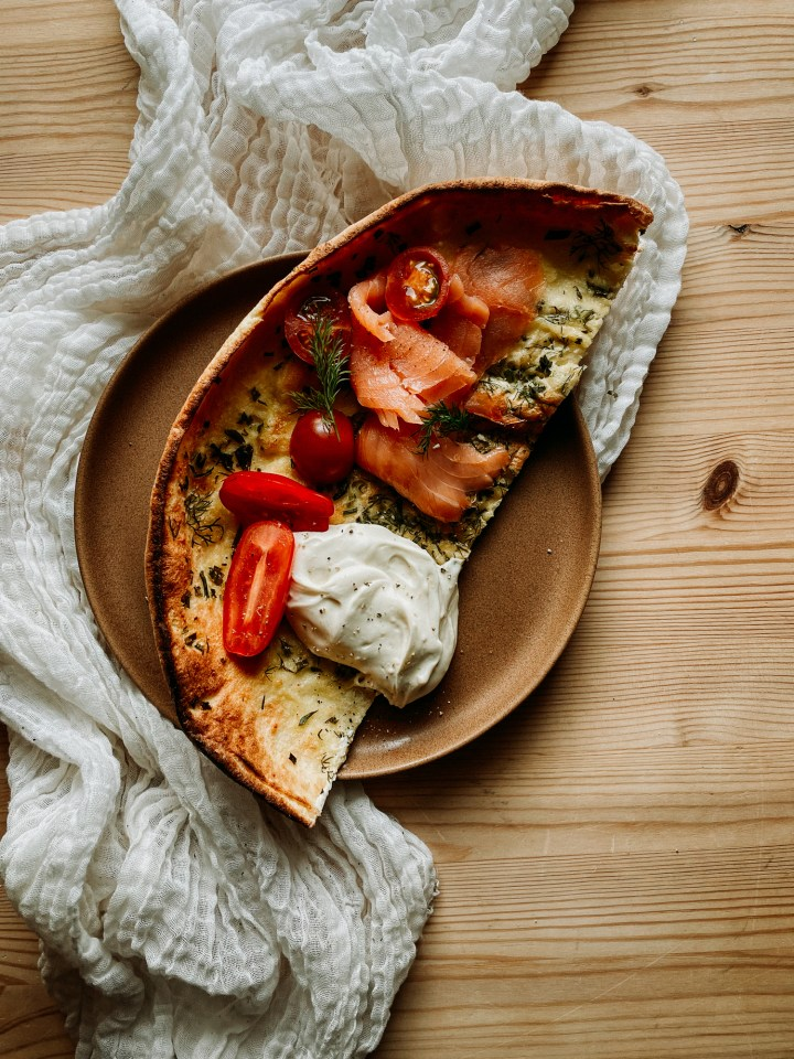 a half of a Savory Buttermilk Herb Dutch Baby topped with smoked salmon and mascarpone cheese on a white cloth lines wooden surface