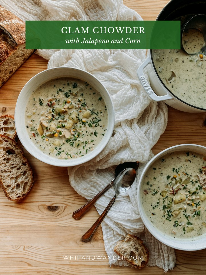bowls of Clam Chowder with Jalapenos and Corn resting on a white cloth next to a dutch oven filled with chowder, bread to the left of the bowls, and two spoons resting between the bowls