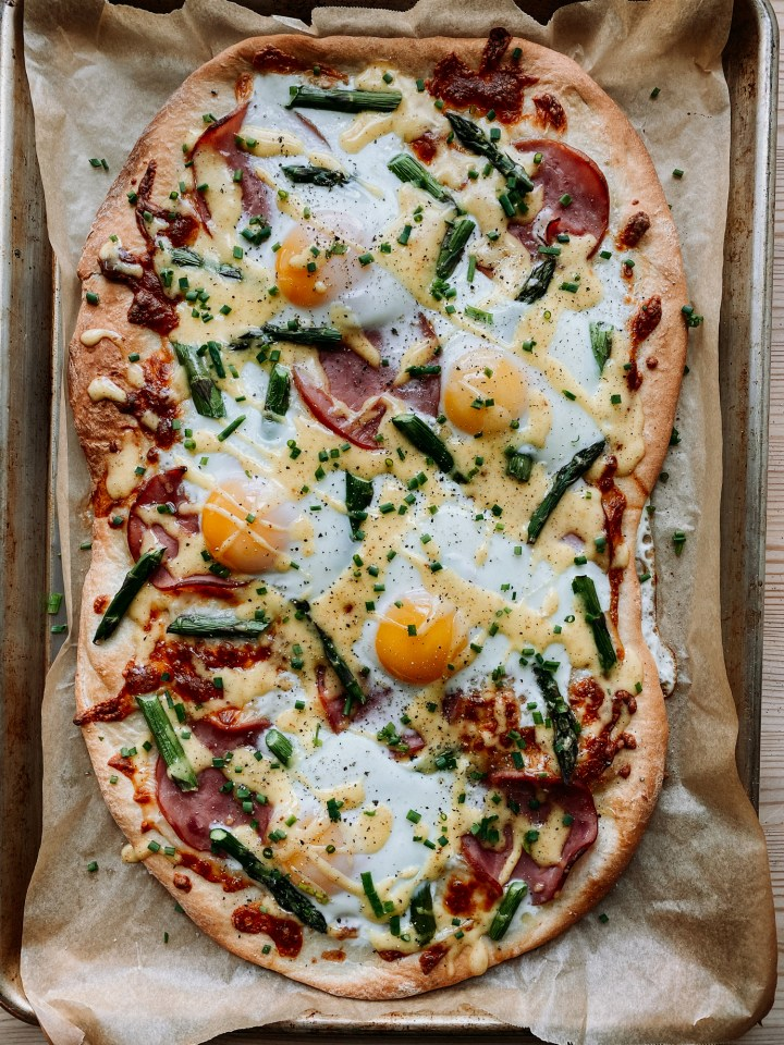a Eggs Benedict Pizza resting on a brown parchment paper covered baking tray