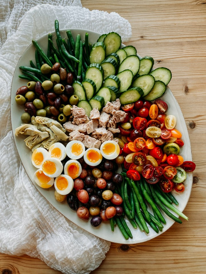 a white platter with Tuna Salad Nicoise resting on a white piece of fabric on a wooden surface