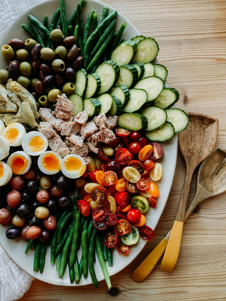a platter with cucumber, tomatoes, green beans, potatoes, eggs, artichoke hearts, and olives