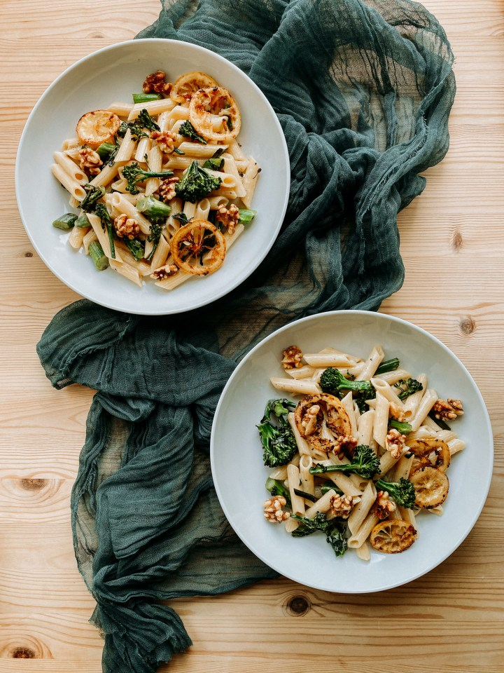 two white pasta bowls filled with Gorgonzola Pasta with Browned Butter Lemon and Broccolini and walnuts resting on a green cloth topped wooden table