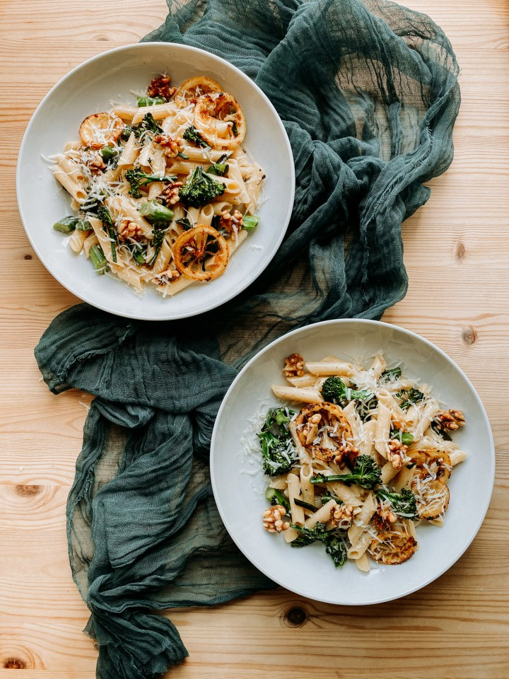 two white pasta dishes that contain Gorgonzola Pasta with Browned Butter Lemon and Broccolini both resting on a piece of green gauzy cloth on a wooden table
