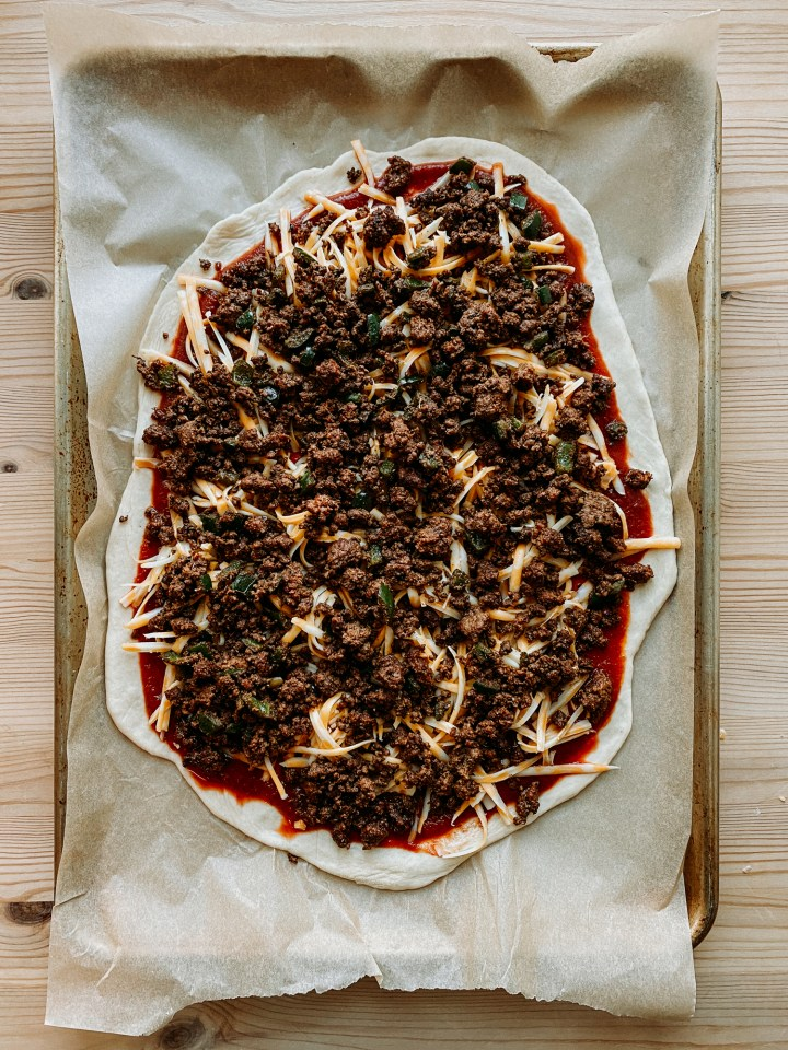 a pizza topped with taco meat and colby jack cheese