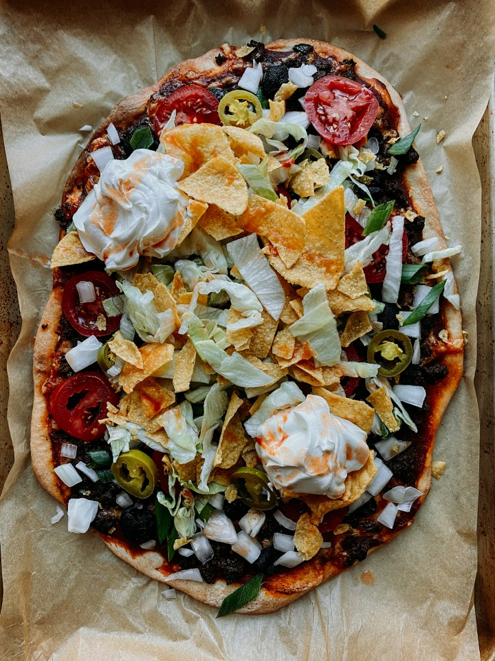 a taco pizza topped with sour cream and tortilla chips on a baking sheet