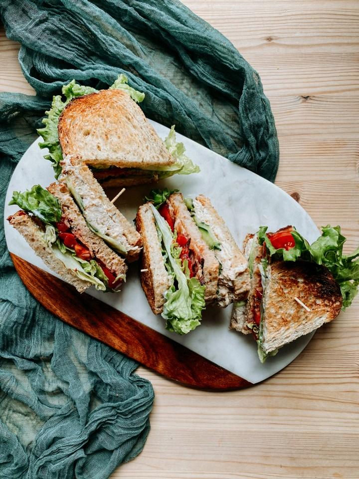 a pile of crab club sandwiches on a cutting board